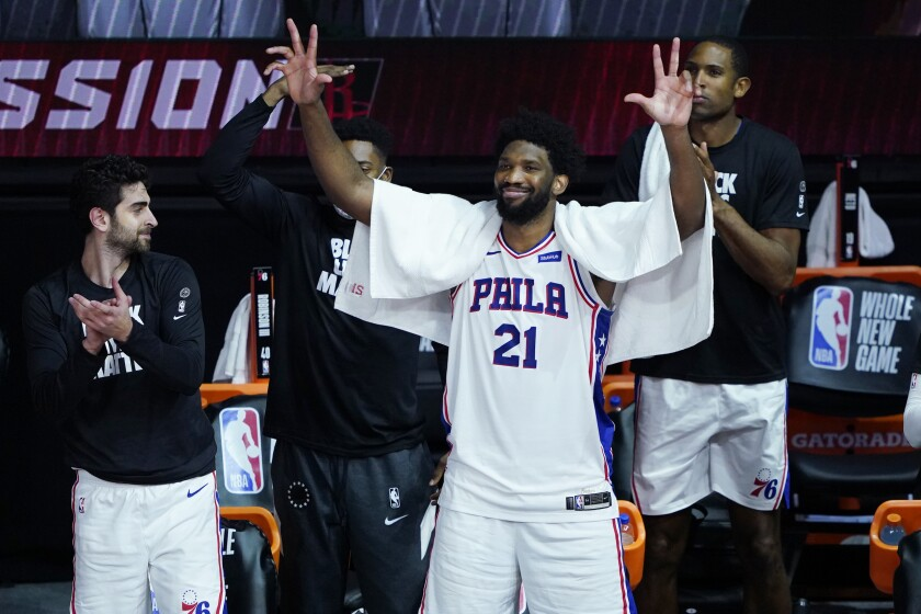 Philadelphia 76ers' Joel Embiid (21) celebrates from the bench during the second half of an NBA basketball game against the Houston Rockets, Friday, Aug. 14, 2020, in Lake Buena Vista, Fla. (AP Photo/Ashley Landis, Pool)