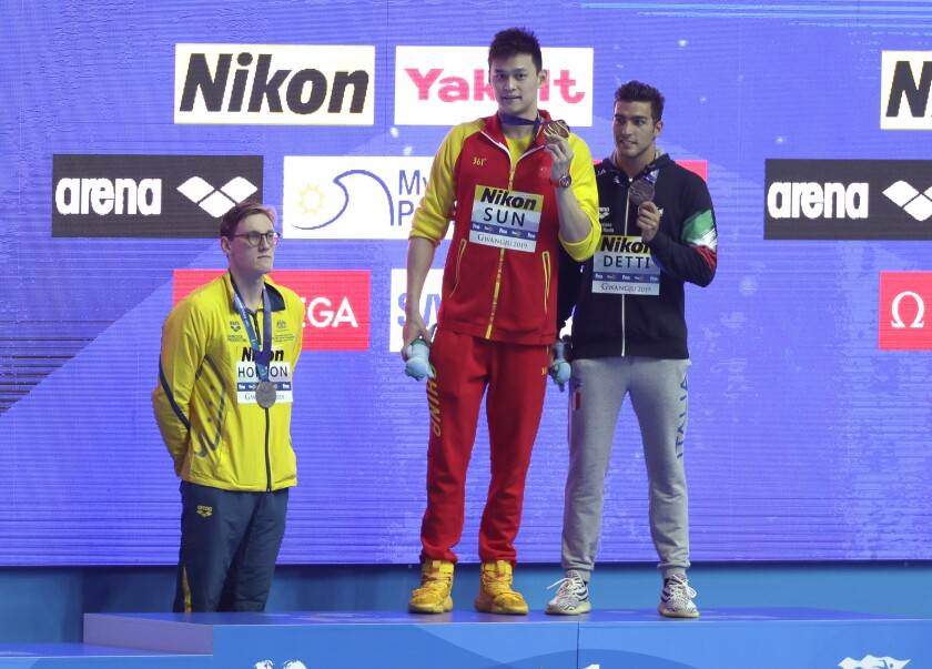 FILE - In this July 21, 2019, file photo, China's Sun Yang, center, holds up his gold medal as silver medalist Australia's Mack Horton, left, stands away from the podium with bronze medalist Italy's Gabriele Detti, right, after the men's 400m freestyle final at the World Swimming Championships in Gwangju, South Korea. Two years after his controversial podium move at the world swimming championships, Australian Mack Horton still can't seem to shake off questions about the guy he intended to snub. (AP Photo/Mark Schiefelbein,File)