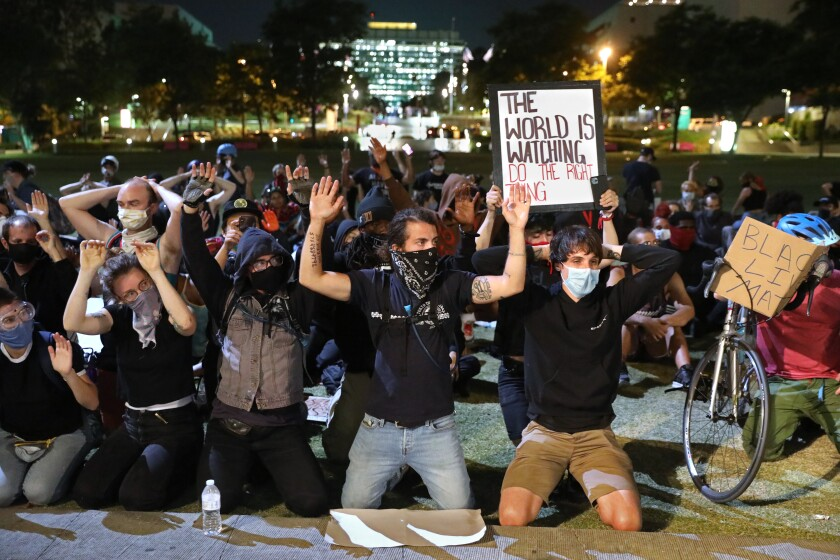 Protesters kneel and hold their hands in the air after dark at Grand Park in downtown Los Angeles