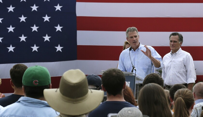 New Hampshire Senate candidate Scott Brown, left, addresses a gathering of supporters with Mitt Romney, the former Republican presidential nominee, at his side during a campaign stop at a farm in Stratham, N.H., on July 2. Brown, who is facing incumbent Democrat U.S. Sen. Jeanne Shaheen, was endorsed by Romney at the event.