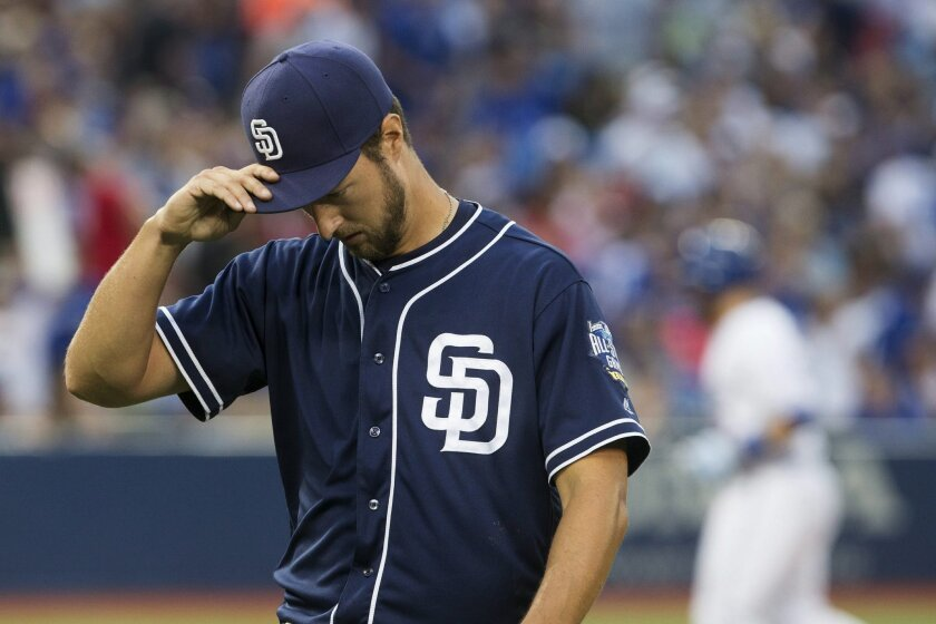 San Diego Padres starting pitcher Colin Rea walks back to the dugout at the end of the fourth inning after giving up a run to a sacrifice fly from Toronto Blue Jays shortstop Troy Tulowitzki in baseball action in Toronto on Monday, July 25, 2016. (Chris Young/The Canadian Press via AP)
