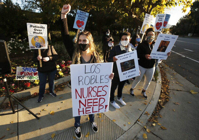 Medical professionals hold signs during a street-corner protest.