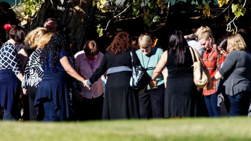 Evacuated workers pray in a circle on the fairway of San Bernardino Golf Club, across the street from where they narrowly escaped a mass shooting at the Inland Regional Center. This was among the first of several important photos taken by Gina Ferazzi on Dec. 2, 2015.