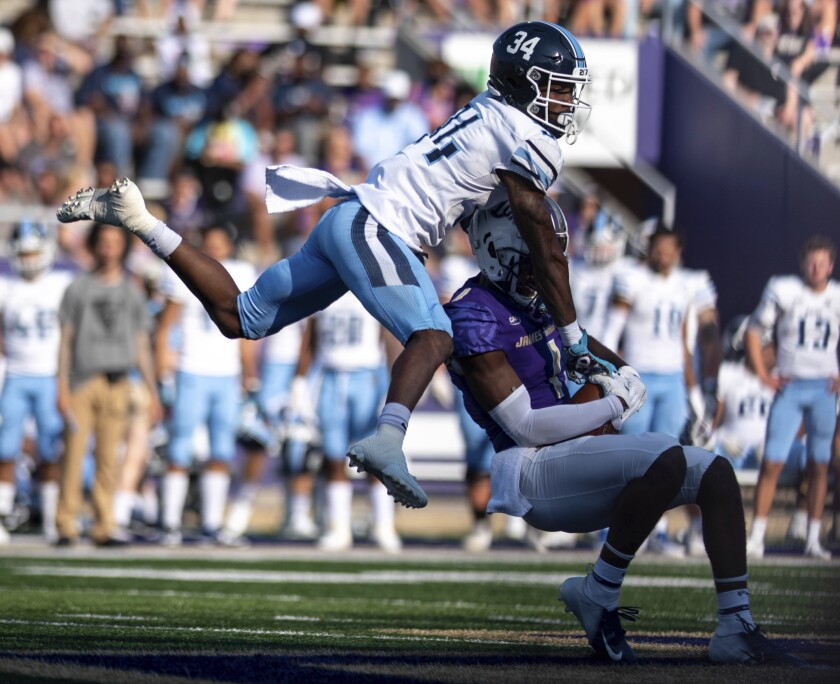 Maine defensive back Kolubah Pewee Jr. (34) leaps while defending against James Madison wide receiver Scott Bracey (1) during the first half of an NCAA college football game in Harrisonburg, Va., Saturday, Sept. 11, 2021. (Daniel Lin/Daily News-Record via AP)