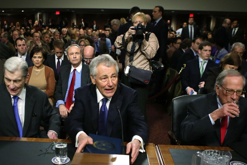 Former Sen. Chuck Hagel (R-Neb.), center, takes a seat at his confirmation hearing to become the next secretary of defense on Capitol Hill. During the nearly eight hours of Hagel¿s hearing, no more than 10 minutes were spent on Afghanistan.