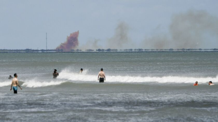 A cloud of orange smoke rises over nearby Cape Canaveral Air Force Station as seen from Cocoa Beach, Fla., Saturday. SpaceX reported an anomaly during test firing of its Dragon 2 capsule at the LZ-1 landing site at Cape Canaveral Air Force Station.