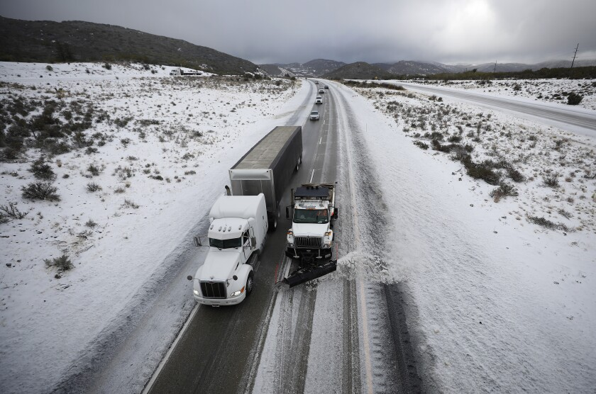 A snowplow clears Interstate 8 at Laguna Summit during a steady snow on Monday.