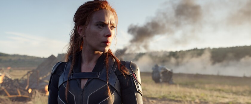 A woman in body armor in front of a burning landscape