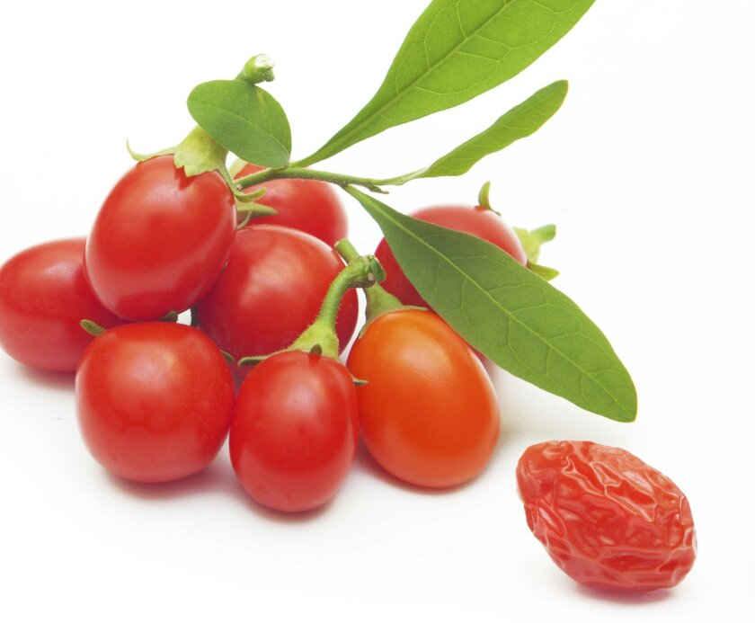 Bright red goji berries resemble tiny tomatoes.