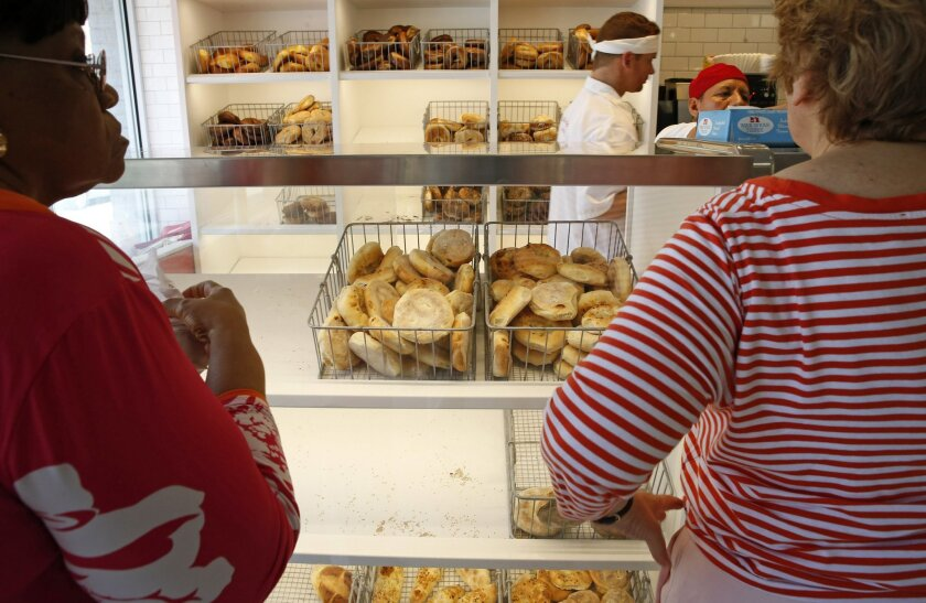 Customers wait at the counter to place an order food at Kossar's Bagels and Bialys in New York on Thursday, May 26, 2016. Located in the Lower East Side, a traditional immigrant neighborhood, Kossar's is known more for it's bialys than bagels. (AP Photo/Kathy Willens)