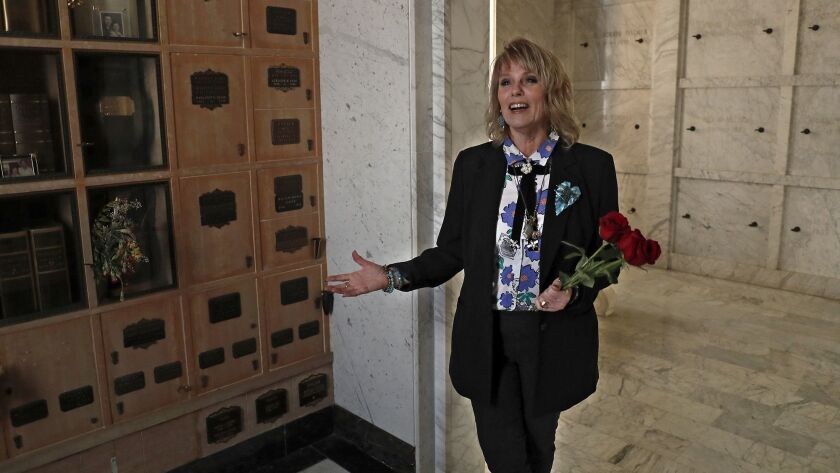 Jill Ann Lloyd, a funeral celebrant and service director, stands beside her mother's remains in the