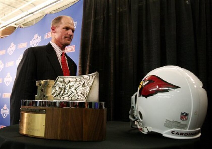 Arizona Cardinals coach Ken Whisenhunt walks past the George S. Halas Trophy for the National Football Conference Championship and an Arizona Cardinals helmet after a news conference at the team's football training facility on Friday, Jan. 16, 2009, in Tempe, Ariz.  The Cardinals face the Philadelp