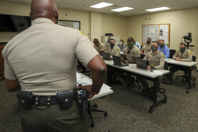 The deputy chief of the San Bernardino County sheriff, Horace Boatwright, left, speaks during a morning meeting.