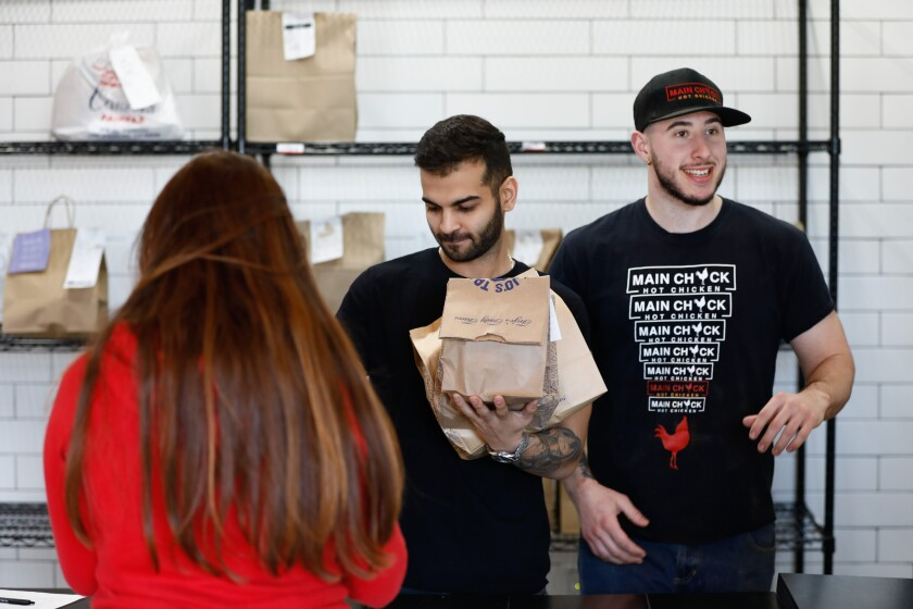 Colony manager Sean Aslany, center, hands a pickup order from Trejo's Tacos to a customer as Calvin Skarlat of Main Chick Hot Chicken talks to a customer at Colony.