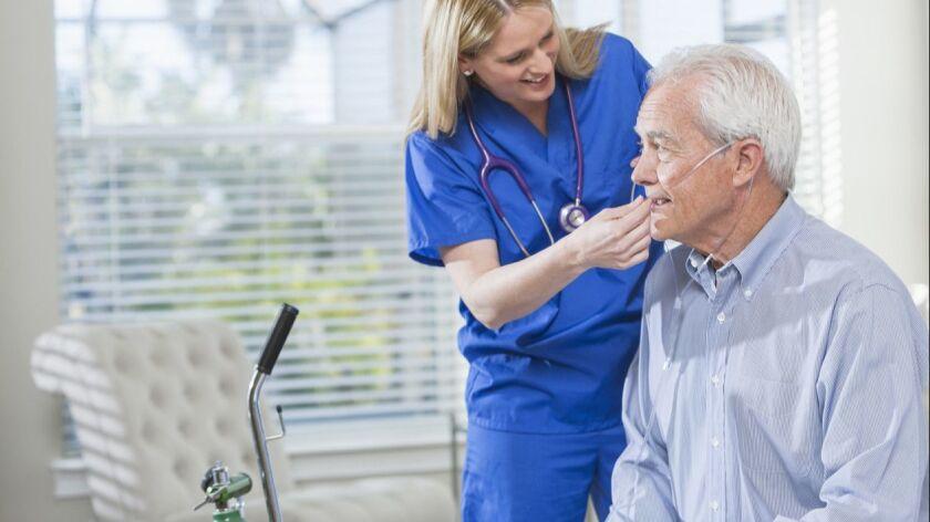 Home healthcare nurse helping elderly man with oxygen