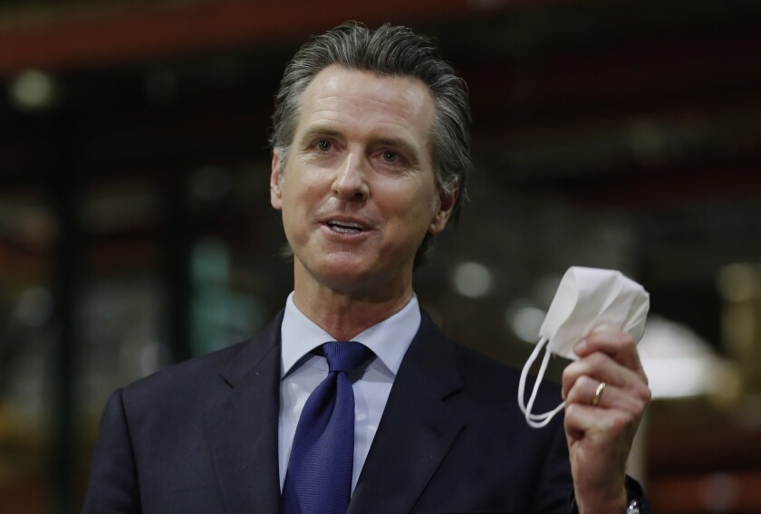 FILE - In this June 26, 2020, file photo, California Gov. Gavin Newsom displays a face mask.