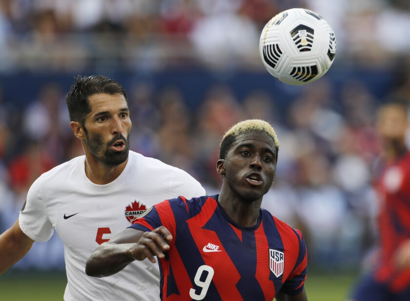 Canada defender Steven Vitoria (5) and U.S. forward Gyasi Zardes (9) chase down the ball during the second half of a CONCACAF Gold Cup soccer match in Kansas City, Kan., Sunday, July 18, 2021. (AP Photo/Colin E. Braley)
