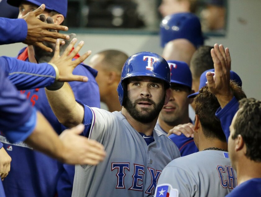 FILE - In this Sept. 8, 2015, file photo, Texas Rangers' Mitch Moreland, center, is greeted in the dugout after he hit a solo home run during the second inning of a baseball game against the Seattle Mariners, in Seattle. Moreland has agreed to a $5.7 million, one-year contract with the Texas Ranger