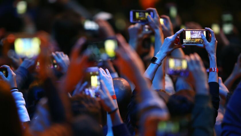 UFC fans in Las Vegas take photos with their camera phones during weigh ins for UFC 207 in December 2016.