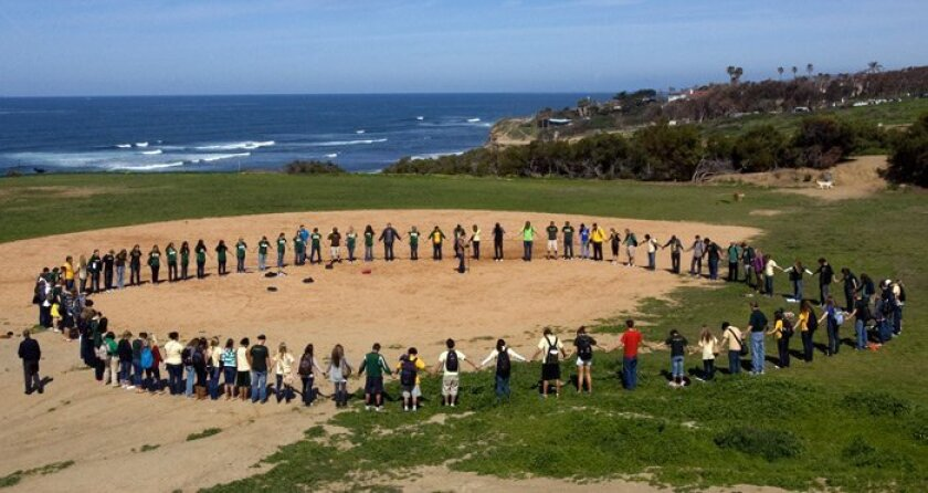 Athletes from PLNU form a prayer circle on the school's former softball field at the end of a march that protested the cutting of four sports at the university.