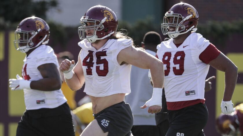 USC linebacker Porter Gustin, 45, and defensive lineman Christian Rector, 89, run to the workout station during spring practice at Howard Jones Field.