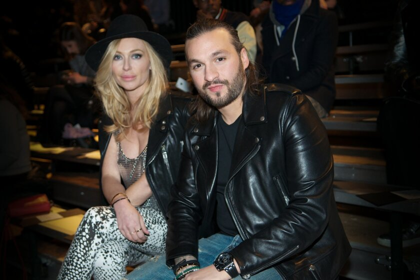 FILE - In this Feb. 11, 2014 file photo, Isabel Adrian and Steve Angello, right, attend EN|NOIR Fall/Winter 2014 Runway Show at Park Avenue Armory in New York. Angello announced Friday, March 7, 2014, that his Size Records will roll out more than 170 songs for free to fans in America. (Photo by Sco