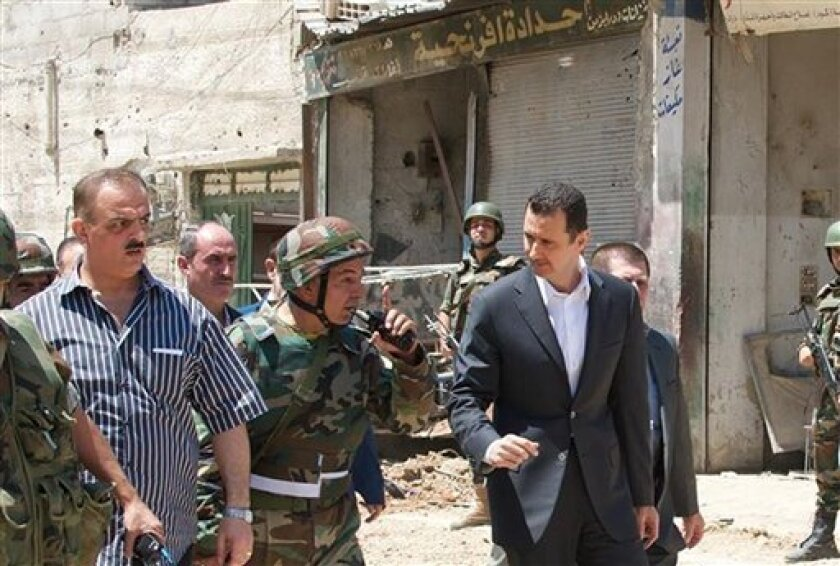 This image posted on the official Facebook page of the Syrian Presidency on Thursday, Aug. 1, 2013 purports to show Syrian President Bashar Assad walking with soldiers with during Syrian Arab Army day in Darya, Syria. Syrian state-run TV says Assad has visited a tense Damascus suburb to inspect his troops on the occasion of the country's Army Day. The visit on Thursday is Assad's first known public trip outside the capital, his seat of power, since he visited the Baba Amr district in the central