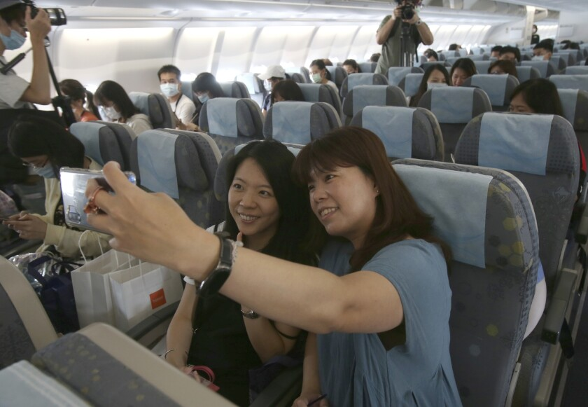 Participants take selfies in the cabin during a mock trip abroad at Taipei Songshan Airport in Taipei, Taiwan, Tuesday, July 7, 2020. Dozens of would-be travelers acted as passengers in an activity organized by Taiwan's Civil Aviation Administration to raise awareness of procedures to follow when passing through customs and boarding their plane at Taipei International Airport. (AP Photo/Chiang Ying-ying)