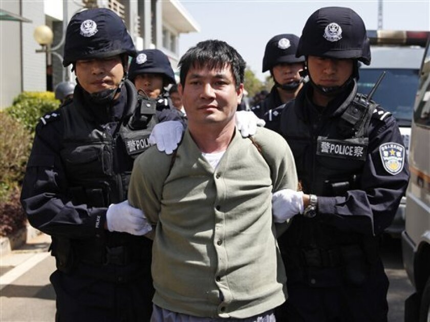 In this photo released by China's Xinhua News Agency, Myanmar drug lord Naw Kham, center, and three of his accomplices, unseen, are taken to the execution chambers where they will receive lethal injection in Kunming, capital of southwest China's Yunnan Province, Friday, March 1, 2013. China execute