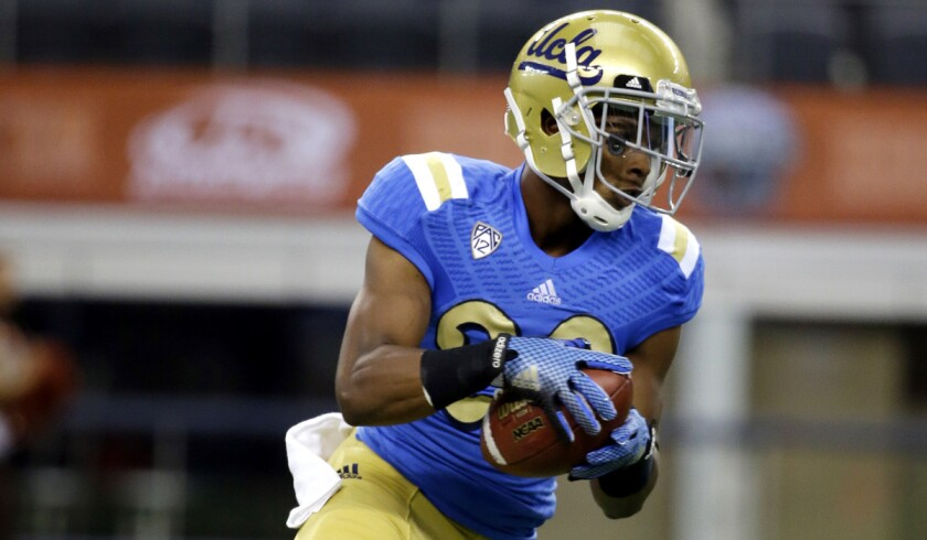 """UCLA defensive back Justin Combs, son of Sean """"Diddy"""" Combs, carries the ball after grabbing a pass during warmups before a game against Texas on Sept. 13, 2014."""
