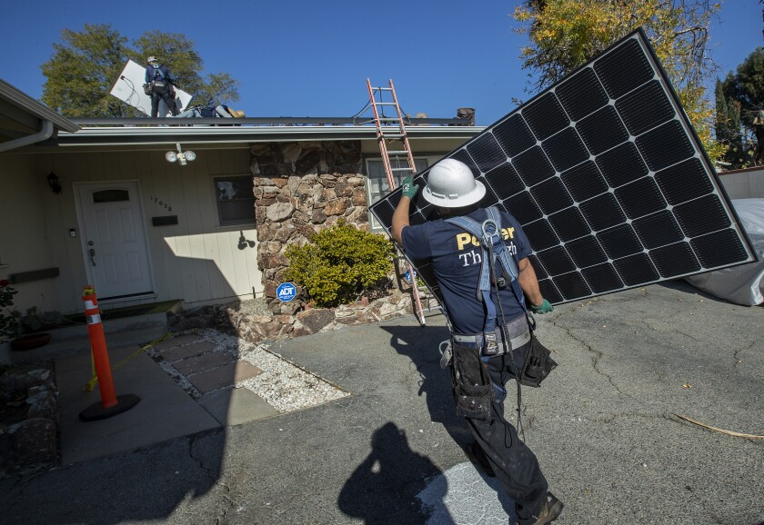 A worker carries a solar panel toward a house