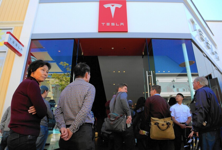 Car buyers at a La Jolla dealership wait in line last month to plunk down $1,000 to reserve Tesla's newest electric car, the $35,000 Model 3 sedan.