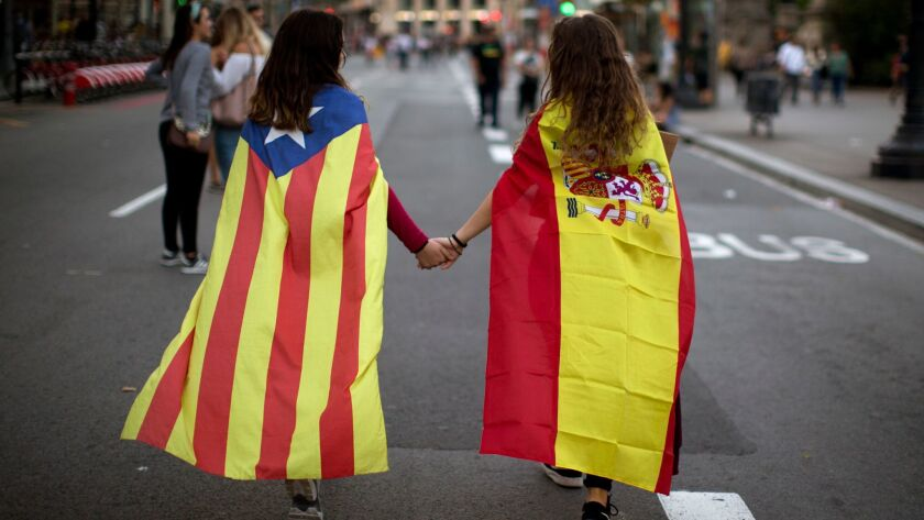 In this Tuesday Oct. 3, 2017 photo, Irene Guszman, 15, wearing a Spanish flag and Mariona Esteve, 14