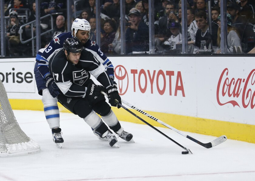 Kings forward Milan Lucic skates with the puck while Jets defenseman Dustin Byfuglien defends him during the second period of a game on April 9.