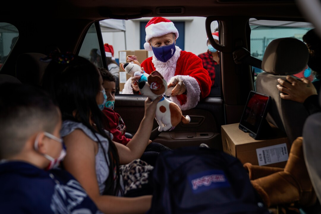 Austin Beutner, dressed as Santa Claus, hands out gifts to kids in a car.