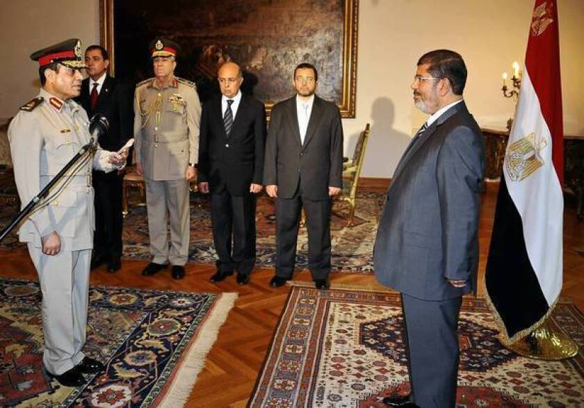 Egyptian President Mohamed Morsi swears in Lt. Gen. Abdel Fattah Sisi as minister of defense in Cairo.