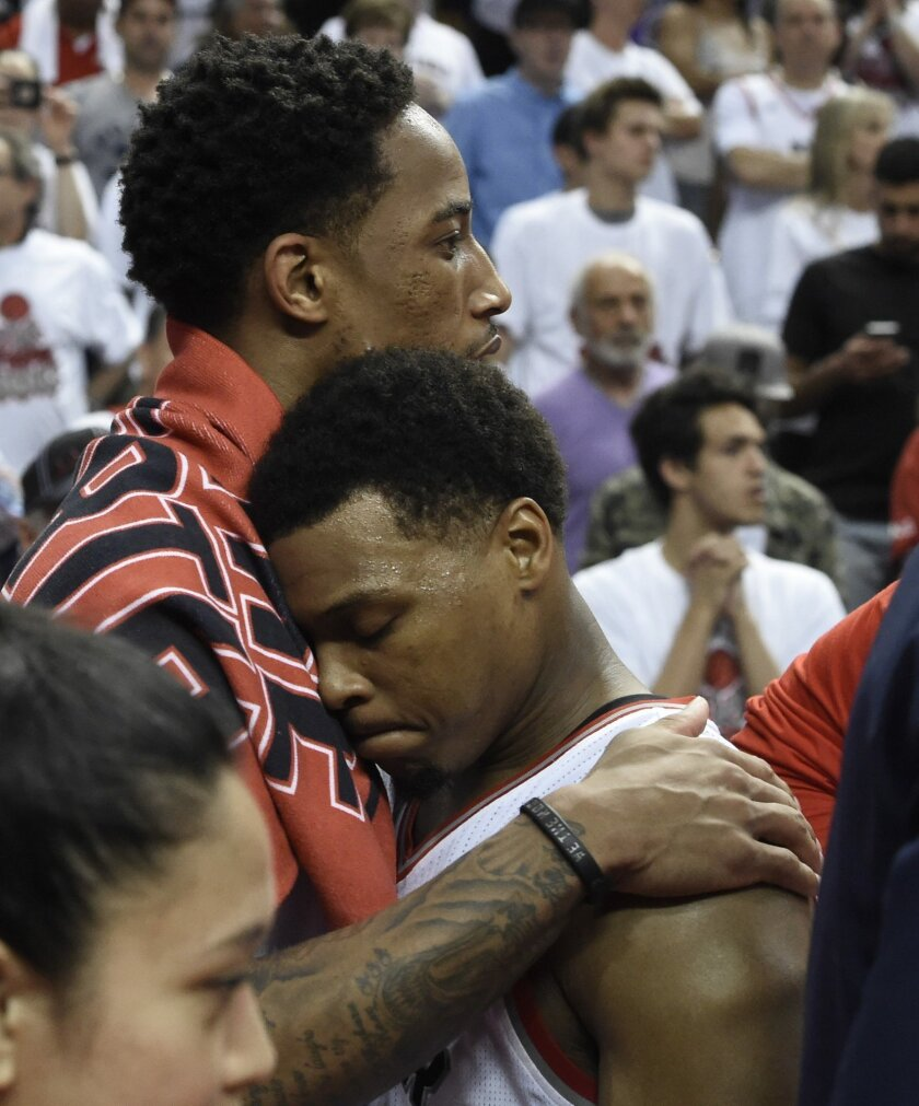 Toronto Raptors guard DeMar DeRozan, left, hugs Kyle Lowry after Game 6 of the NBA basketball Eastern Conference finals, Friday, May 27, 2016, in Toronto. The Cleveland Cavaliers won 113-87 and advanced to the NBA Finals. (Frank Gunn/The Canadian Press via AP)