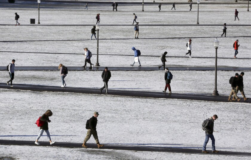 FILE - In this Dec. 11, 2019, file photo Virginia Tech students walk across the Drillfield in the snow in Blacksburg Va. Income-driven repayment plans help more than 8 million federal student loan borrowers afford their monthly payments. But these borrowers can still run into trouble if they don't update, or recertify, their income information on time annually. (Matt Gentry/The Roanoke Times via AP, File)
