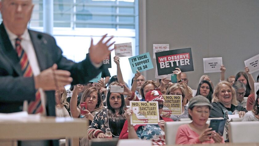 "Supporters and opponents of Senate Bill 54, a California ""sanctuary state"" law, hold up signs as U.S. Rep. Dana Rohrabacher (R-Costa Mesa) speaks during a Newport Beach City Council meeting April 10. Newport is one of several Orange County cities that have opposed the law."