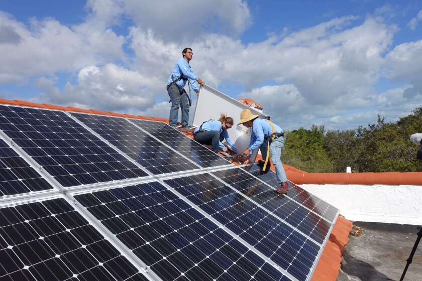 Workers install solar panels on a rooftop on Feb. 20 at a home in Palmetto Bay, Fla.