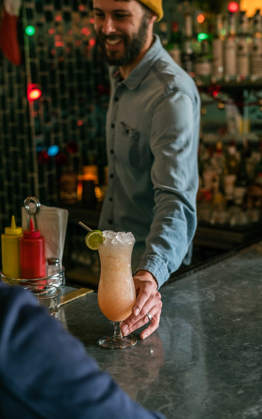 Co-owner Jordan Brownwood serves a cocktail made with fresh guava from the family's Nopalito Farm in Valley Center.