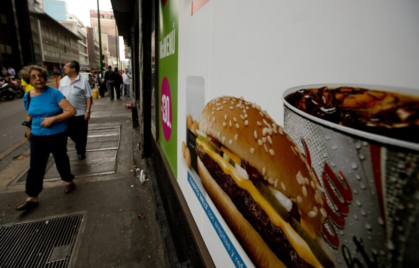 FILE - In this Jan. 6, 2015 file photo, a customer glances at a McDonalds' banner menu showing a burger accompanied by arepas or corn cakes, instead of fries, in Caracas, Venezuela. Fast food lovers in shortage-plagued Venezuela are rejoicing they can once again buy greasy French fries at McDonald'