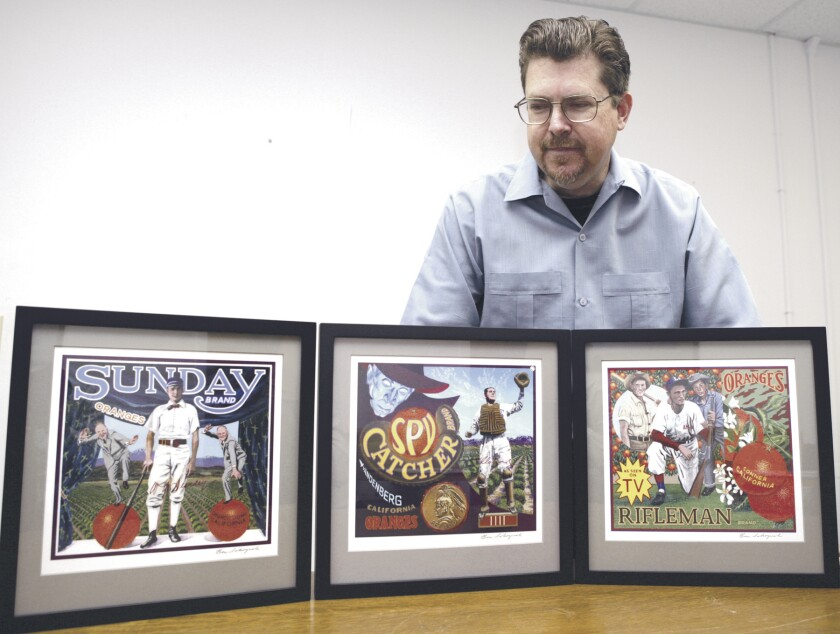 Terry Cannon, of the Baseball Reliquary, looks over some of Pasadena artist Ben Sakoguchi's work.