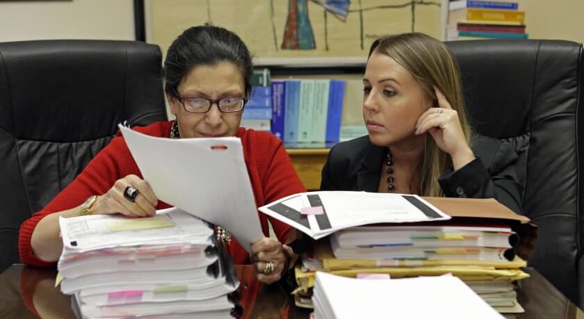 Fotografía del 16 de julio de 2015 de las abogadas Grisel Ybarra (izquierda) y Mónica Barba Neumann mientras revisan documentos en su oficina en Miami. Ybarra y Neumann representan a varios clientes que podrían ser deportados a Cuba. (Foto AP/Alan Díaz)