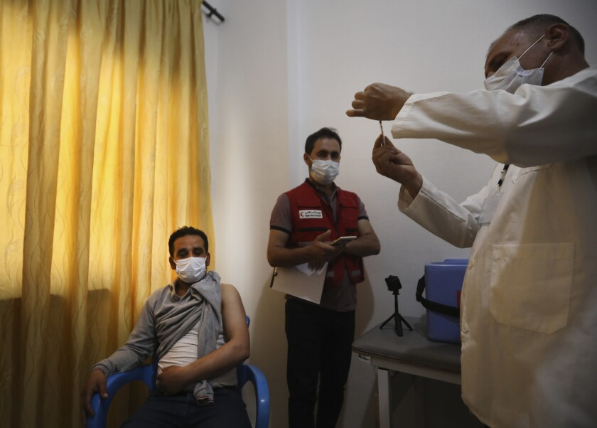 A Syrian health staff, right, prepares a shot of AstraZeneca COVID-19 vaccine to be given for a man, left, at Ibn Sina Hospital, in Idlib town, northwestern Syria, Saturday, May 1, 2021. The inoculation campaign against COVID-19 kicked off in Syria's last rebel-held enclave in the country's northwest, with a 45-year-old front line nurse becoming the first to receive the UN-secured Jabs on Saturday. (AP Photo/Ghaith Alsayed)