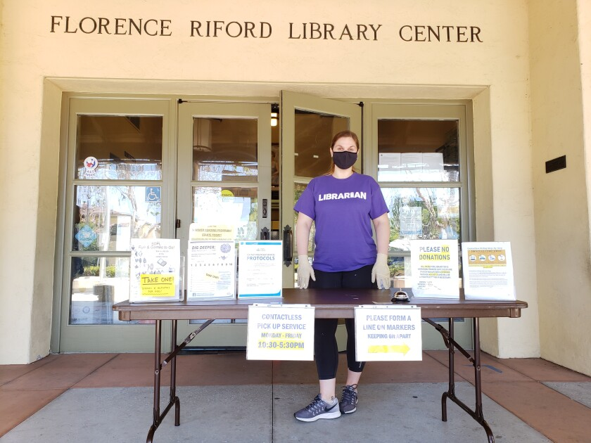 Youth Services Librarian Dana Sanchez stands at the contactless pickup table at the La Jolla/Riford Library in July.