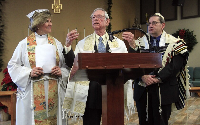 Rabbi Ben Leinow speaks as he, Reverend Laura Sheridan-Campbell, left, and Cantor Larry Kornit lead a combined Christmas Eve and First Night of Hanukkah service called A Service of Light and Peace in Carlsbad on Saturday.