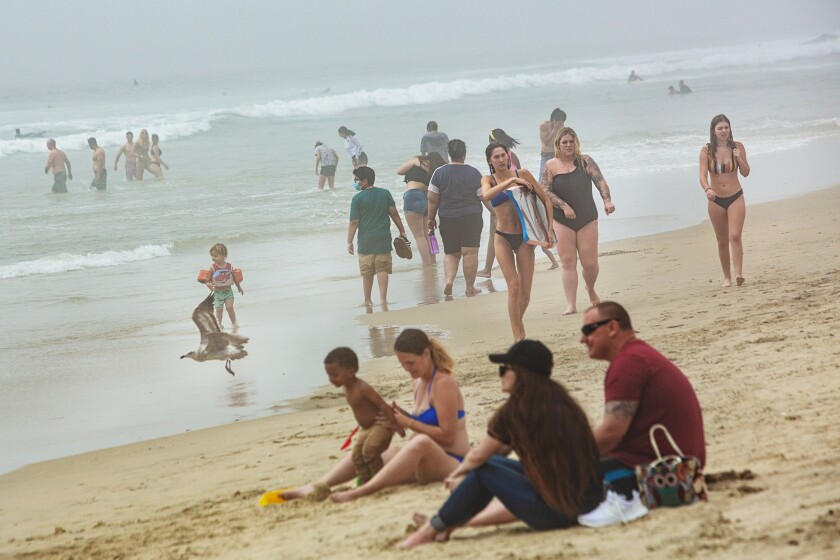 After being on lockdown for over a month because of the coronavirus pandemic, people begin to congregate at Huntington Beach on Sunday.
