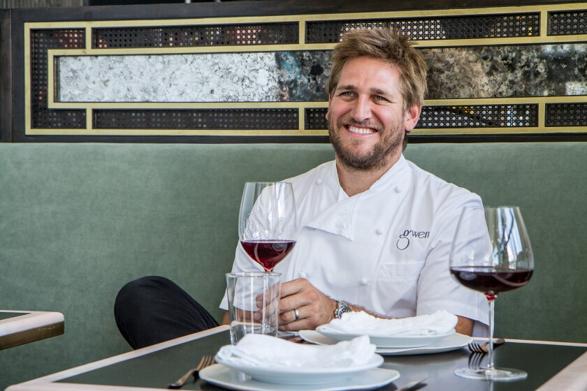 A smiling man in a chef's shirt sits at a restaurant table with two place settings and glasses of red wine