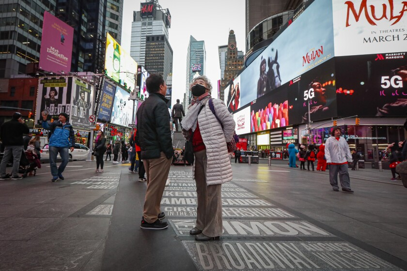 A pedestrian wearing a face mask stops in Times Square, Thursday, March 12, 2020, in New York. New York City Mayor Bill de Blasio said Thursday he will announce new restrictions on gatherings to halt the spread of the new coronavirus in the coming days. For most people, the new coronavirus causes only mild or moderate symptoms. For some it can cause more severe illness. (AP Photo/John Minchillo)